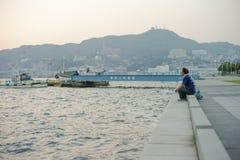 Nagasaki, Japan: 31 augustus, 2016 - zitting van de Portret de Aziatische mens op de kust en het kijken uit de oceaan in de winde stock foto