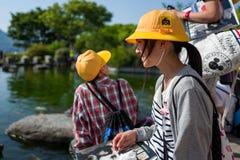 Nagasaki Japan - Maj 18: Den oidentifierade skolaflickan med den gula hatten ler i Glover Garden på Maj 18, 2017 i Nagasaki Royaltyfri Bild