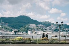Nagasaki, Kyushu, Japan, East Asia - Students going home after school in a background of beautiful landscape with sea and mountain stock photography