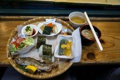 Nagashi Somen,日本流动的面条,被服务寒冷通过竹子长的水道一半裁减用调味汁,新鲜的烤鱼 免版税库存图片