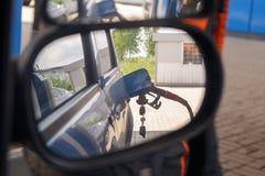 Nagedacht in de zijspiegel van een auto van brandstofpijp om brandstof in auto bij benzinestation opnieuw te vullen stock fotografie