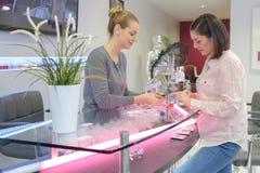 Nagelband för kvinnamanikyristklippningar spikar på klienten royaltyfria foton