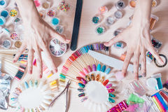 Nagelkunstkonzept Frau, die Dekoration auf den Nägeln auf weißer Tabelle macht Stockfoto