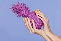 Nagelmaniküre Hand mit den stilvollen Nägeln, die purpurrote Ananas halten stockfotos