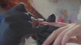 Nagelmeister entfernen Nagellack im Schönheitssaal mit elektrischem Dateinagel stock footage