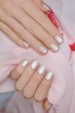 Nageln Sie Kunst Schöne weibliche Hand mit weißer Maniküre lizenzfreie stockbilder