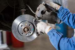 Nagelneue Bremsscheibe auf Auto in einer Garage Automechanikerreparatur Lizenzfreie Stockfotos