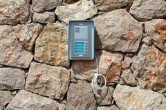 Nagelneue Türeinstieg-Gegensprechanlage angebracht an der traditionellen Steinwand mit dem Hängen von den elektrischen Drähten, d stockfotos