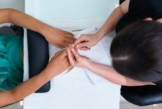 Nagelpflege, Häutchenausschnitt in einem Schönheitssalon stockbilder