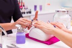 Nagelsaalfrauen-Nagellack entfernen mit Gewebe stockfoto