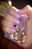 Nagelt lila Farbe auf dem Hintergrund der Tasche mit dem Schmuck Lizenzfreie Stockfotos