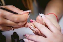 Nagelverzorging, manicure in een schoonheidssalon Stock Afbeeldingen