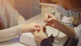 Nagelverzorging in salon De meester past gel-lak op de spijkers van de cliënt toe Stock Foto