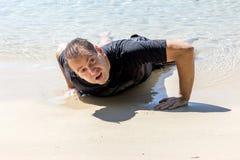 Nageur épuisé rampant sur le bord de la mer photo libre de droits