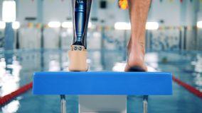 Nageur masculin avec la prothèse bionique réchauffant près d'une piscine clips vidéos