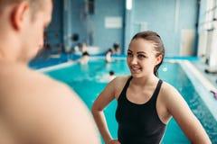 Nageurs parlant sur la formation contre la piscine photo libre de droits