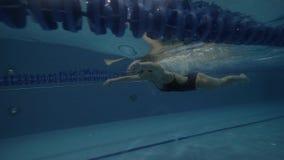 Nageuse de femme dans la brasse de flottement de maillot de bain noir sous l'eau dans la piscine clips vidéos