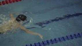Nageuse de femme dans les lunettes flottant la brasse dans le poo de natation de l'eau banque de vidéos