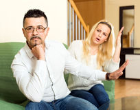 Nagging wife. Wife is having a quarell with her husband over his job and salary. She is talking loudly while he is sitting turned away from her tired Stock Photo