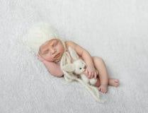 Nagi sypialny dziecko w kapeluszu z zabawką na białej koc Zdjęcie Royalty Free