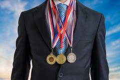 Nagradzający pomyślny biznesmen jest ubranym wiele medale obraz stock