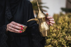 Nahöstliche Frau, die arabischen Kaffee anbietet Stockbilder