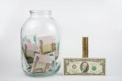 Nah an dem Dreiliter-Glas, das mit Geld ist ein gefüllt wird, Stapel Münzen nahe bei ihm ist eine Banknote von zehn Dollar Stockbilder
