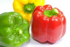 Nah herauf drei frische Gemüsepaprikas auf weißem Hintergrund lizenzfreie stockfotografie