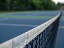 Nah oben fokussiert von einem Tennisplatznetz mit Hintergrund in der Unschärfe lizenzfreies stockbild