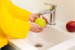 Nah oben von den Händen der Frauen, die grünen Apfel in der Wanne waschen lizenzfreies stockfoto
