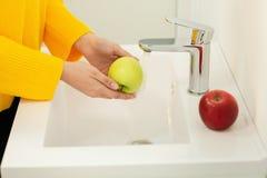 Nah oben von den H?nden der Frauen, die gr?nen Apfel in der Wanne waschen lizenzfreies stockfoto