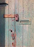 nah oben von einer alten Holztür mit grüner verblaßter Farbe und einem rostigen geschlossenen Vorhängeschloss- und altenmetallbri lizenzfreie stockfotos