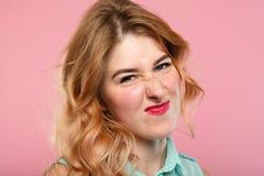 Nah unbeeindrucktes Mädchen, das Nase knitternd Gesicht verzieht stockfotografie