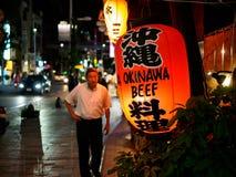 Naha, Japan - November18: Unbekannter Mann geht auf die Straßen vor Okinawa Beef-Laterne am 18. November 2015 in Naha lizenzfreie stockbilder