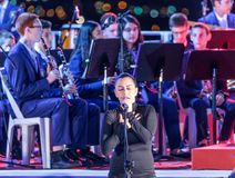 The singer, accompanied by a brass band, performs a song at a commemorative ceremony in the Memorial Site To the Fallen in Israel. Nahariyya, Israel, April 17 royalty free stock image