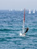 Young athlete in a black tracksuit exercising in windsurfing in the Mediterranean sea in Nahariya, Israel. Nahariyya, Israel - Februar 10, 2018 : Young athlete Stock Photo