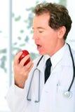 Nahaufnahme-älterer Doktor Eating Red Apple stockbild