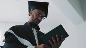 Nahaufnahme, Ansicht von unten, indischer Absolvent der Akademie im Umhang liest ein Diplom stock video