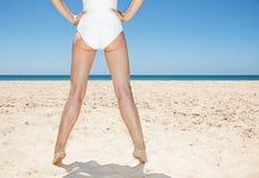 Nahaufnahme auf Beinen der Frau im weißen Badeanzug am sandigen Strand Lizenzfreies Stockbild