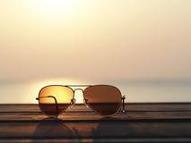 Nahaufnahme auf Brillen mit fokussierter und unscharfer Landschaftssonnenuntergangansicht Lizenzfreie Stockfotografie