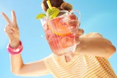 Nahaufnahme auf Cocktail in den Händen der jungen Frau Sieg zeigend Stockbilder