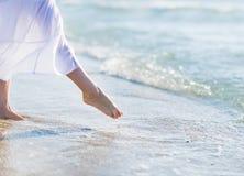 Nahaufnahme auf dem Bein der Frau stehend auf Seeufer Stockfotografie