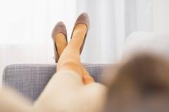 Nahaufnahme auf dem Bein der jungen Hausfrau legend auf Couch Stockfotografie