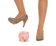 Nahaufnahme auf dem Frauenbein, das piggy Bank bricht Lizenzfreies Stockfoto