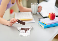 Nahaufnahme auf dem Mädchen, das Schokolade beim Studieren isst Lizenzfreie Stockbilder