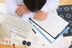 Nahaufnahme auf dem müden Arzt, der auf Tabelle schläft Stockbild