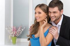 Nahaufnahme auf dem Mann, der Ohrring auf dem Ohr des Mädchens betrachtet Stockbild
