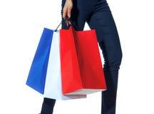 Nahaufnahme auf dem Modehändler, der mit Einkaufstaschen auf Weiß geht lizenzfreie stockfotografie