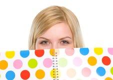 Nahaufnahme auf dem Studentenmädchen, das hinter Notizbuch sich versteckt Stockbilder