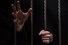Nahaufnahme auf den Händen des Mannes sitzend im Gefängnis Lizenzfreies Stockbild